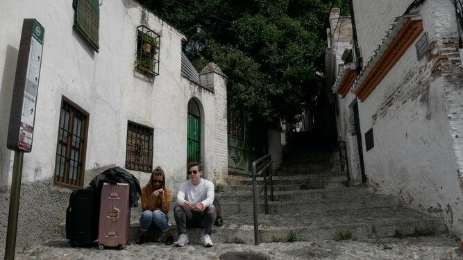 Dos turistas esperan que pase uno de los autobuses que cubren el barrio del Sacromonte